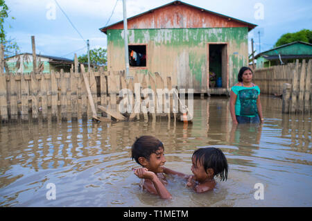 2015 flooding in Brazilian Amazon - children play in the dirt waters of Acre river at Taquari district, Rio Branco city, Acre State. Floods have been affecting thousands of people in the state of Acre, northern Brazil, since 23 February 2015, when some of the state's rivers, in particular the Acre river, overflowed. Further heavy rainfall has forced river levels higher still, and on 03 March 2015 Brazil's federal government declared a state of emergency in Acre State, where current flood situation has been described as the worst in 132 years. - Stock Image