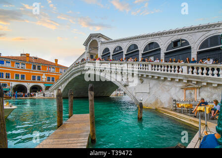Tourists line the Rialto Bridge overlooking the Grand Canal as a sea gull perches on a pier and watches a couple dine at a cafe in Venice, Italy - Stock Image