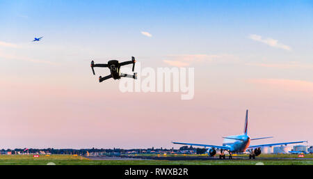 Unmanned drone flying near runway at airport while commercial airplane takes off leading to possible collision - digital composite. - Stock Image