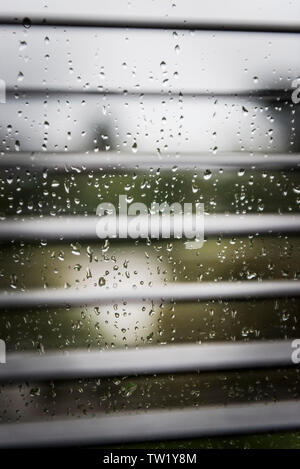 Raindrops on a window pane seen through blinds. - Stock Image