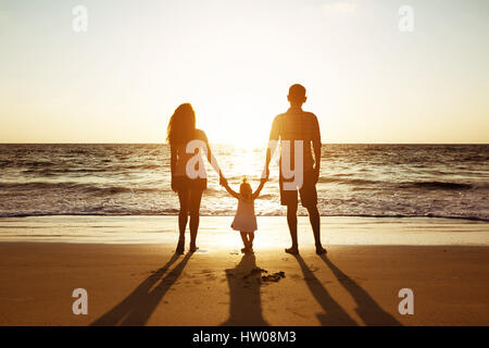 Family of father mother and daughter sunset sea silhouettes - Stock Image