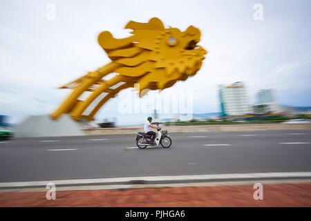 Panning of motorbike riders in front of Dragon Bridge in Da Nang, Vietnam. The dragon's head spews out flames and sprays of water every weekend, and i - Stock Image
