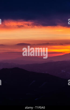 Beautifully colored sky at dusk, with mountains layers - Stock Image