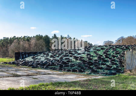 Silage mound with cover held in place by old tyres.The fermented, green forage fodder is used to feed cattle & sheep - Stock Image