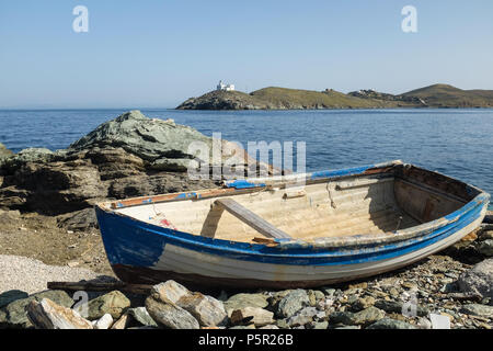 Small Wooden Boat Moored on Rocky Shore on the Island of Kea ( Tzia ) with Lighthouse in the distance, Aegean Sea's Cyclades archipelago, Greece. - Stock Image