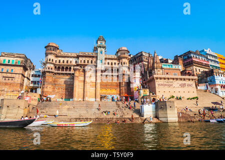 VARANASI, INDIA - APRIL 12, 2012: Colorful boats and Ganges river bank in Varanasi city in India - Stock Image