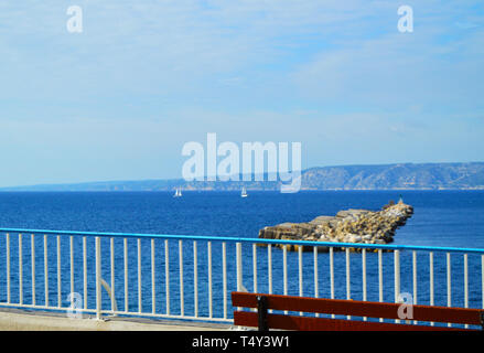View of the calm blue sea with small yachts in the sea Bay from the waterfront. Luxury summer holiday on the French Riviera, a copy of the space. - Stock Image