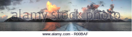 Panorama from boat of clouds over Tilos island at sunset in Greece - Stock Image
