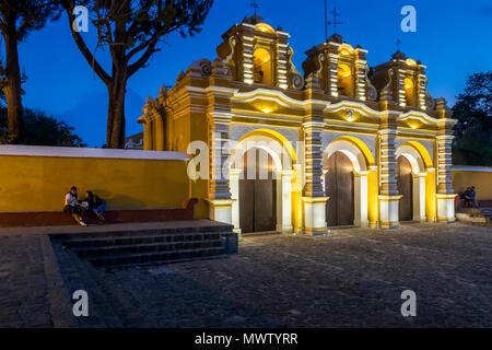 Illuminated entrance gate of the chapel El Calvario near Antigua at dusk, Guatemala, Central America - Stock Image