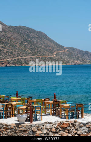 Plaka, Crete, Greece. June 2019. Tables and chairs all empty on the  coast at Plaka a Cretan resort. - Stock Image