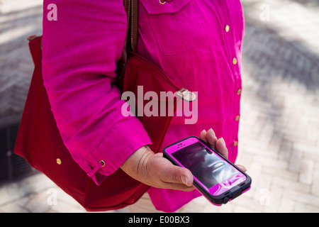 A woman holds an iPhone 5 with a pink protecting case wearing a red bag and a pink blouse in West Palm Beach, Florida. - Stock Image