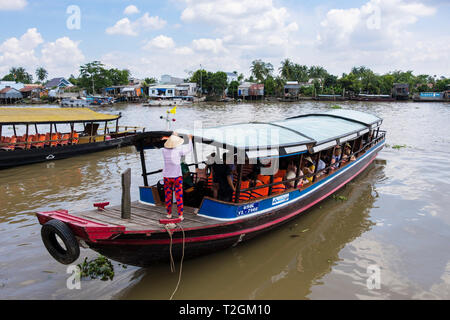 Tourists in traditional boat for river trip in Mekong Delta. Cai Be, Tien Giang, Vietnam, Asia - Stock Image