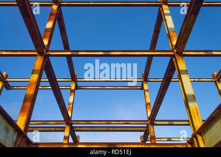 rusting rolled steel joist skeleton of a building outlined against a blue sky - Stock Image