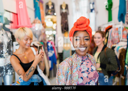 Portrait enthusiastic young woman shopping with friends in clothing store - Stock Image