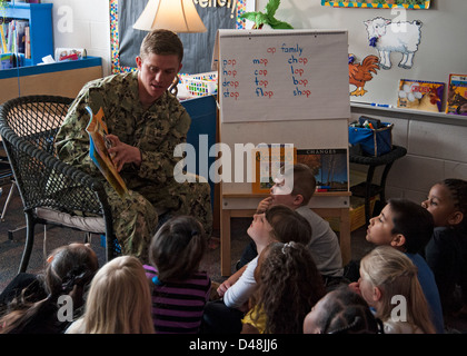 An officer reads to elementary school students. - Stock Image