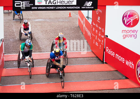 London, UK. 28th April 2019. Wheelchair Athletes cross the Finish Line of The 39th London Marathon in The Mall. Credit: Keith Larby/Alamy Live News - Stock Image