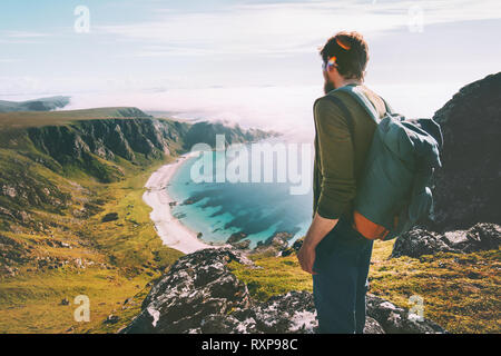 Man admires ocean beach aerial view solo traveling active lifestyle hiking adventure summer vacations in Norway outdoor - Stock Image