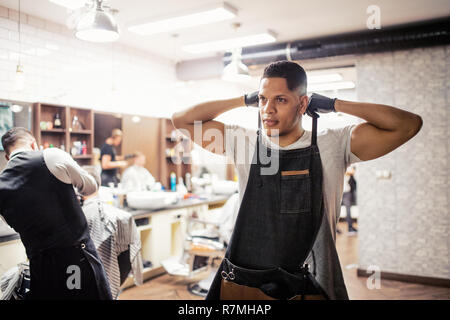 Young handsome hispanic haidresser and hairstylist standing in barber shop. - Stock Image