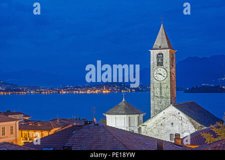 Blue hour view from roof top terrace of Hotel Rosa Baveno Italy with view of church clock tower and Lago Maggiore showing floodlit church and sparklin - Stock Image