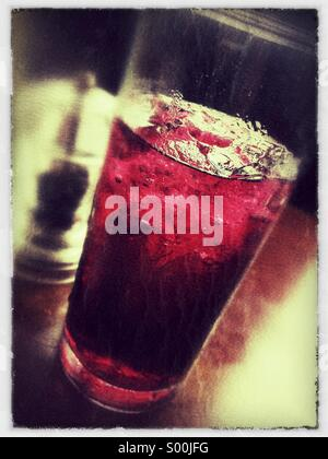 Grungy close up of black currant soft drink on table. - Stock Image