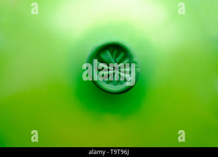 blown up green balloon with tied end - Stock Image