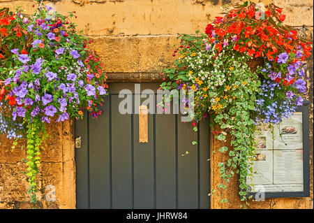 Colourful hanging baskets either side of a doorway in Chipping Campden, Cotswolds - Stock Image