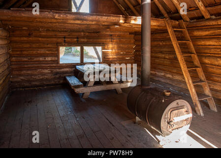 Interior of the historic cabin, built in 1901, in the Olallie Meadows campground in Oregon's Mt. Hood National Forest, lit by the morning sun through  - Stock Image
