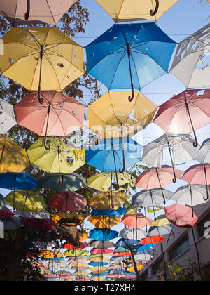 Colorful but sun faded umbrellas providing shade over restaurants and shops in the market in the Turkish Cypriot part of Nicosia. Cyprus - Stock Image