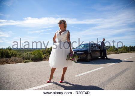 Couple of newlyweds stopped with the car on a lonely road - Stock Image