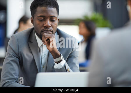 Serious thoughtful handsome young black businessman touching chin while examining report on laptop - Stock Image