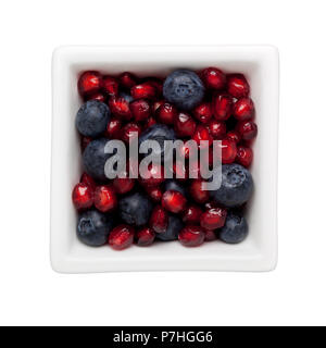 Pomegranate arils and blueberries in a square bowl isolated on white background - Stock Image