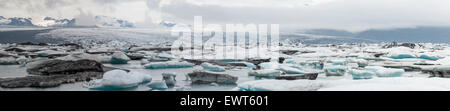 Vatnajokull glacier area high resolution panorama with coloured ice by vulcan ashes. Grey sky with dense clouds. - Stock Image