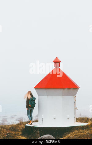 Woman tourist walking near lighthouse Travel lifestyle adventure trip outdoor in Norway foggy seaside on background - Stock Image