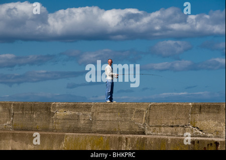 image of fisherman on pier looking at camera - Stock Image