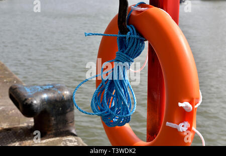 Life saving ring with rope by waters edge on harbour quayside - Stock Image