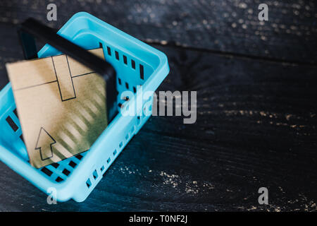 add to cart concept: cardboard online delivery parcel in shopping basket - Stock Image