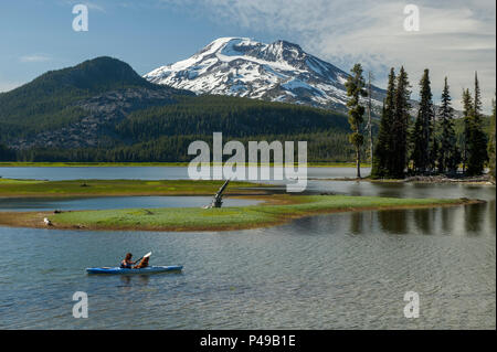 A woman and her dog enjoy a kayak ride on Oregon's scenic Sparks Lake, beneath the South Sister - Stock Image