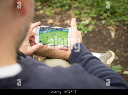 Man watching streaming football game on smartphone in rural location - Stock Image