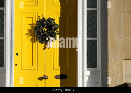 A Christmas wreath fastened to a bright yellw painted house door. Its an old victorian house in Clifton, Bristol - Stock Image