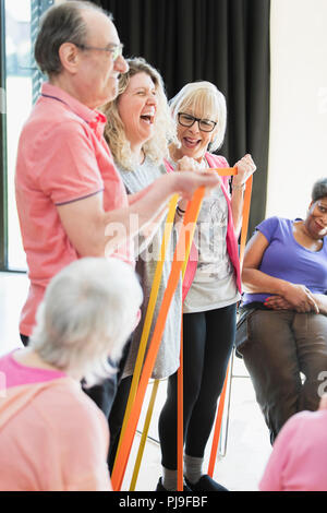 Smiling active seniors and instructor stretching, exercising with straps - Stock Image