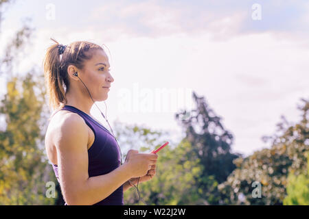 attractive blonde runner woman listening to music before jogging outdoors at park, fitness accessories - Stock Image