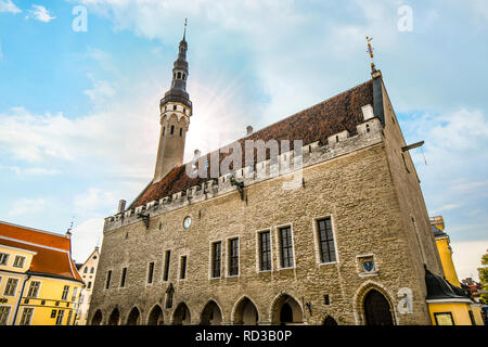 The sun's rays shine behind the tower of the Tallinn Estonia Town Hall, in the town square of the medieval city. - Stock Image