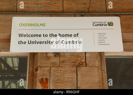 A sign above a platform at Oxenholme station in the Lake District for the University of Cumbria - Stock Image