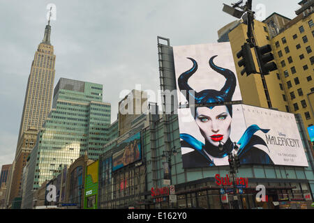 Manhattan, New York, U.S. - May 21, 2014 - A large overhead billboard on 7th Avenue advertises upcoming Disney movie Maleficent, starring actress Angelina Jolie, with Empire State Building at left in background, during a pleasant Spring day in Manhattan. - Stock Image