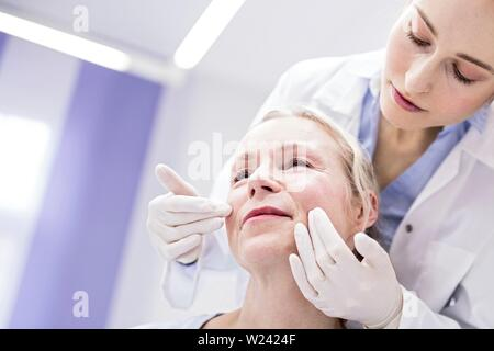 Young female doctor examining patient's face. - Stock Image