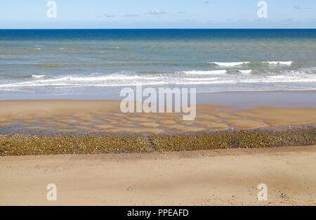 A view of the beach and sea with an ebbing tide on the North Norfolk coast at East Runton, Norfolk, England, United Kingdom, Europe. - Stock Image