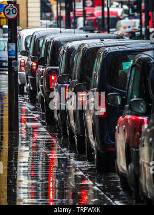London Taxis in the Rain - a queue of London Black Cabs waiting for passengers in the pouring rain - Stock Image