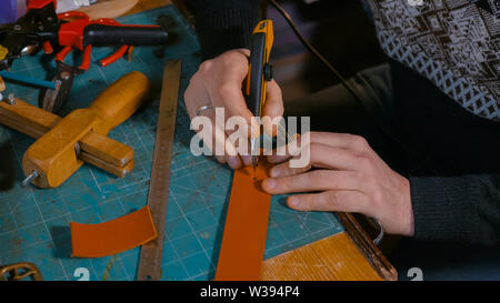 Skinner working with leather belt - Stock Image