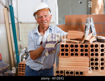 Happy experienced elderly bricklayer posing near red brick stack in building under construction - Stock Image