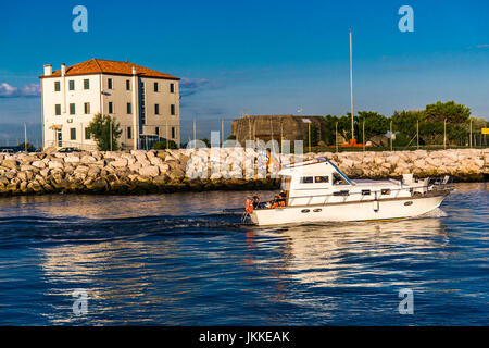 Boat with people and venetian flags sailings on the water. Jesolo, Italy. - Stock Image